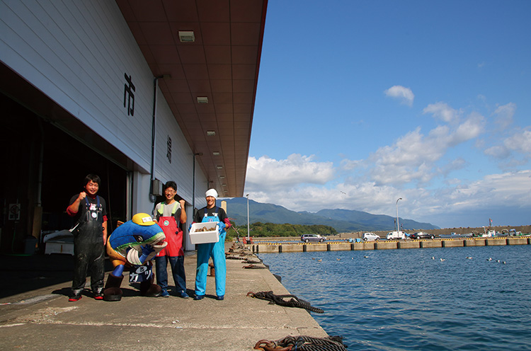 佐渡魚市場でお仕事をしていた若手漁師のみなさんと記念撮影! 漁港は佐渡汽船ター ミナルからも近いので、船を降りてすぐ港町の雰囲気が味わえるのです