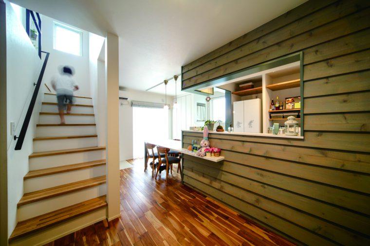 キッチン&ダイニングには冷凍庫が入る広い収納スペースを設置。キッチンを囲う板の色とデザインがポイント