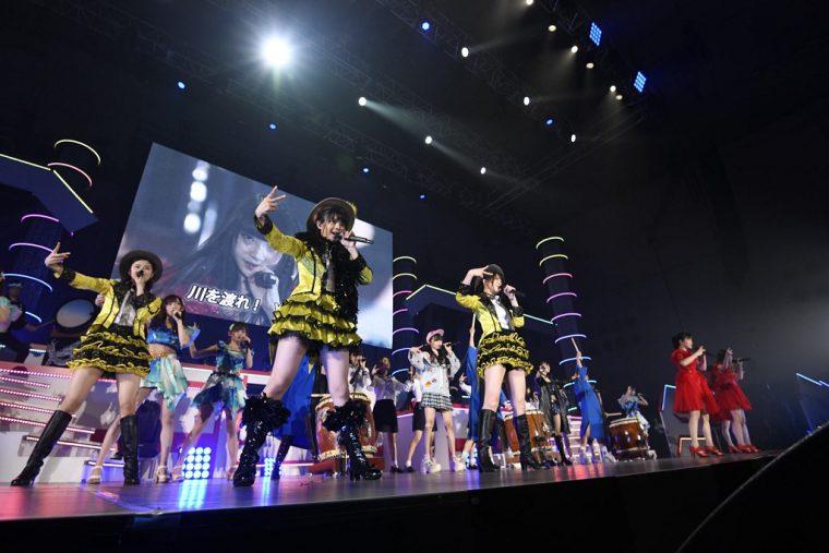 歌が象徴する、黄色、青、赤などの色をまとったメンバーたちがステージに集合! ©AKS