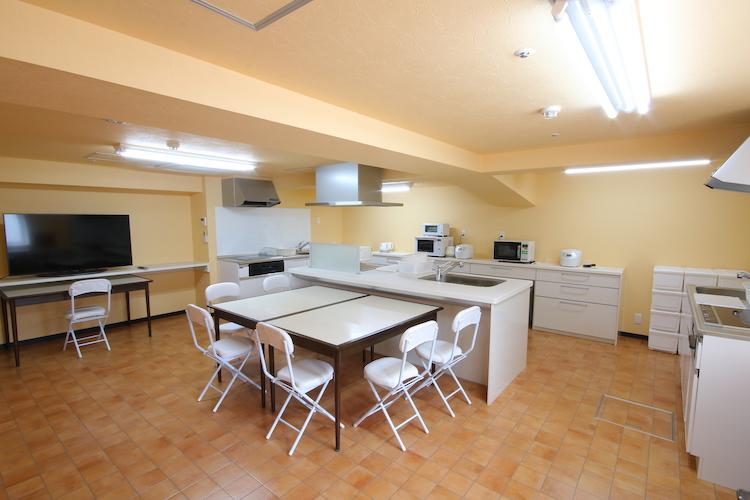 ここは共用キッチン。シンクとコンロ、炊飯器などは3セットあります。大型テレビも用意されているので、ひとりでの食事も寂しくありません。
