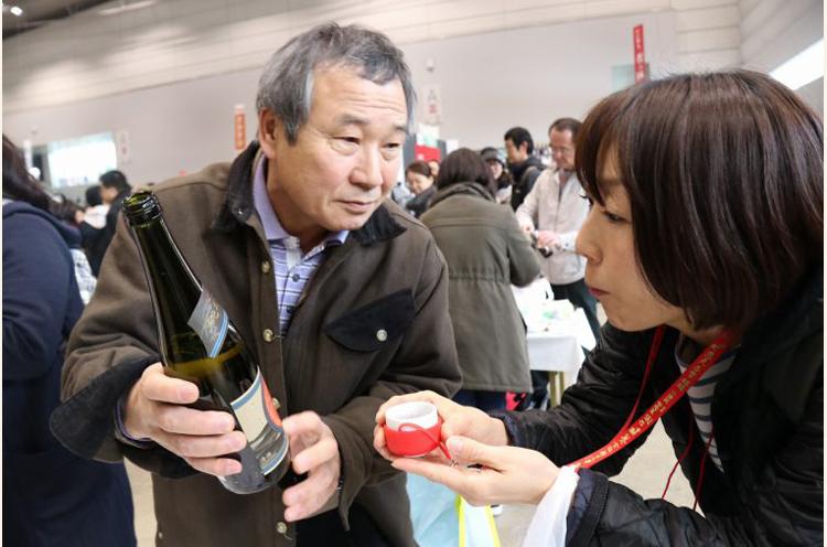 会場で出会った一般の方から、その方が購入されたお酒をすすめられるがままに、遠慮するわけでもなくいただくシモちゃん