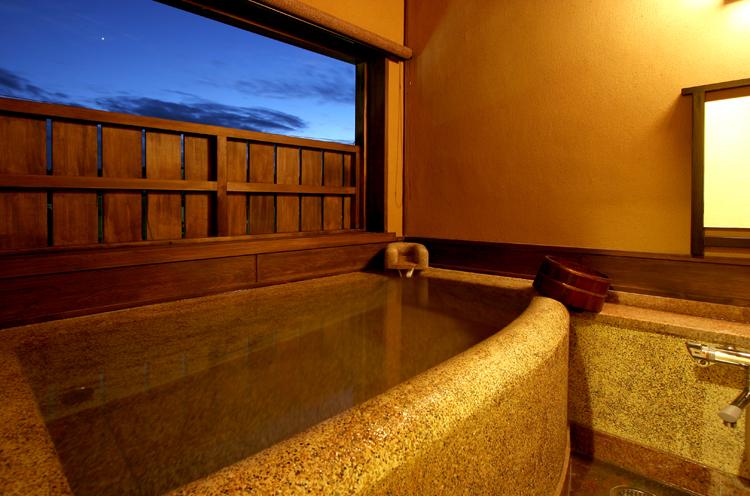 石造りの趣あ る半露天風呂が付いた客室「松風」