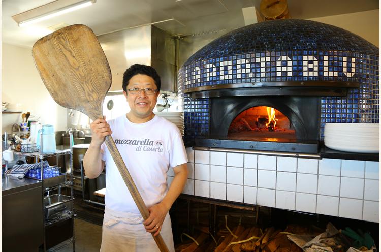 青い薪窯はお店のシンボル。オーナーシェフの坂井友三さん