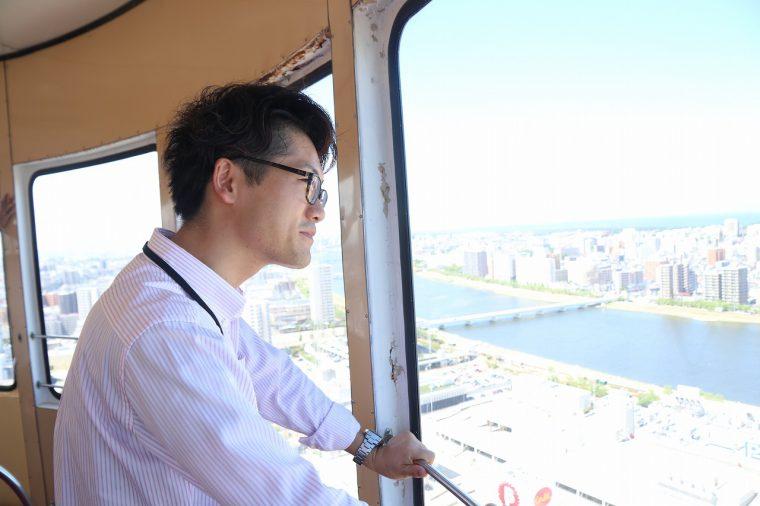 レインボータワーとの別れを惜しむかのように感慨深げに景色を見る、新潟交通事業部の棚橋さん。目に光るのは猛暑ゆえの汗か、それとも惜別の涙か…