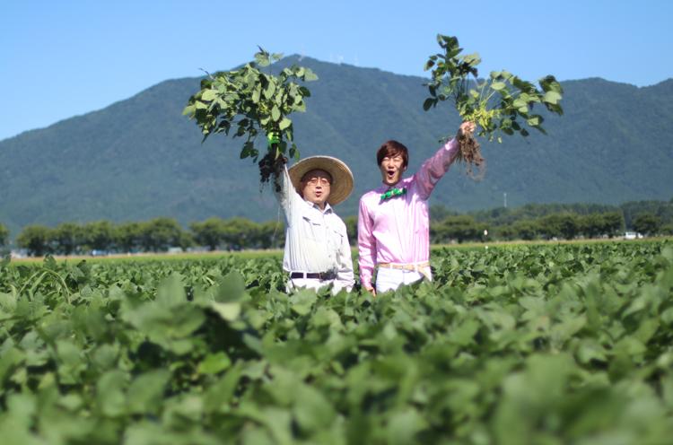 「枝豆とったどー!」弥彦山をバックにおたけびをあげるオチャメな小林村長と僕