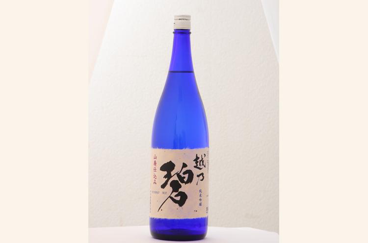 『越乃碧 純米吟醸』(720ml 1,580円~)。神秘の水をイメージしたブルーのボトルで発売! ぬる燗で、味が濃いめのお料理に合わせて飲むとおいしさが広がります