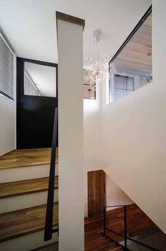 2階リビングへ向かう階段。黒のドアと右上の照明もこだわって選んだ