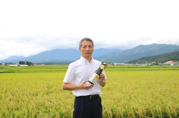 杜氏の早津さん。自身の圃場の前で、越神楽を使った大吟醸をもってにっこり