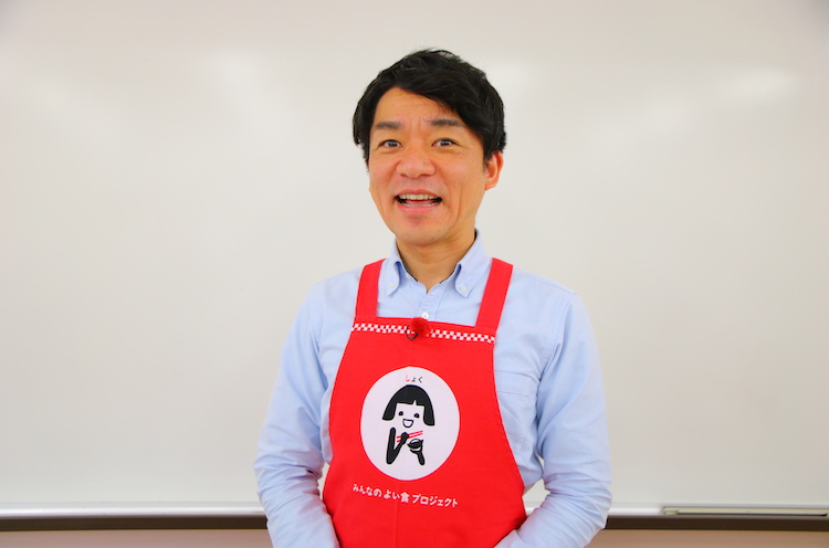 JAの「よい食プロジェクト」シンボルマーク「笑味(えみ)ちゃん」のエプロンがお似合いの飛田アナ