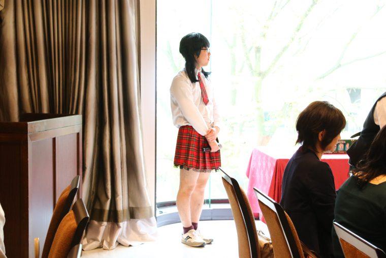 黒髪ツインテでA〇B48のような衣装を身にまとう都子ちゃん。話し方も女子。徹底しとる。