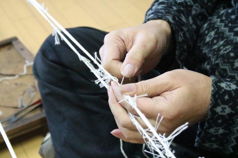 長い糸をひとつひとつ手作業でくくっていきます。糸を染色しすると、くくったことで着色されなかった部分が絣になり、織物の柄として表れるのだそう。