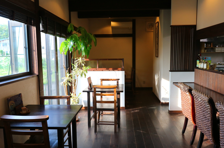 濃茶の木と白い壁の空間に、観葉植物の緑がアクセント。落ち着いた雰囲気でありながら、カフェのようなさわやかさも併せ持つ