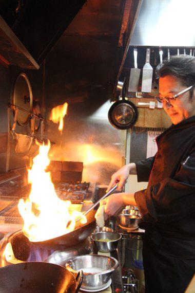 中華鍋でダイナミックに調理するシェフの御手洗さん。ベルギーでの修行経験もある