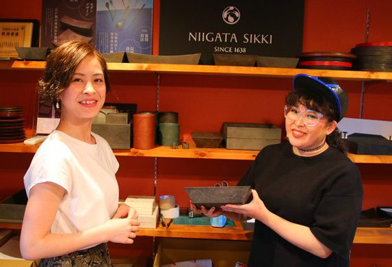 井本さんと、塗師の真田さん(右)をショールームで。ちなみに真田さんが写真で手にしているのが「朧銀塗」のうつわ。 実は現在真田さんしか手掛けることのできない塗りなのです!