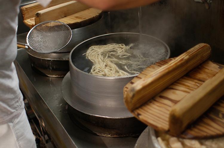 羽釜で麺を躍らせるように茹でて、途中で水を注ぎこみます