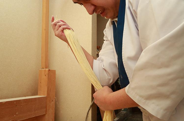 長い麺を手でちょうどよい長さに切断。竜太さんの手から肘までの長さが麺の長さになります