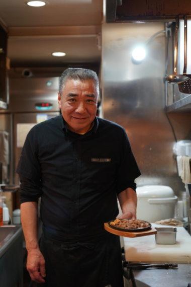 『松坂鉄板焼」を持つ森山聡さん。25 年前にキッチンVに入店。創業者である先代に味を叩き込まれる。Vの味を受け継ぐ唯一の人