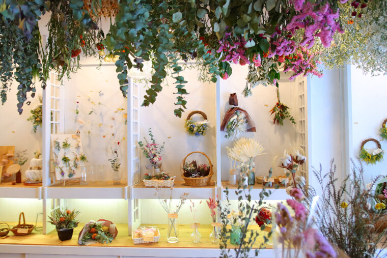 店内。白い壁にカラフルな花が映えます。天井から吊るされた花は制作中のドライフラワー。ディスプレイも兼ねているそう
