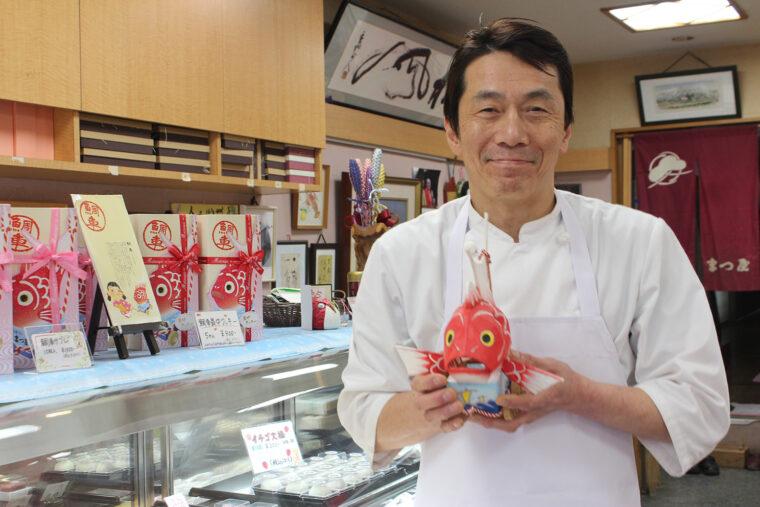 お話をうかがった、お菓子のまつ屋 代表取締役社長の徳井潤之輔さん。現在は和菓子を中心に担当。趣味は映画鑑賞と献血。 鯛車を持っていただきパチリ!