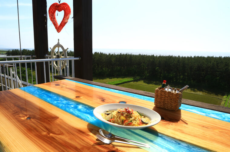 『夏野菜のペペロンチーノ』(1,100円)。ブルーが美しい屋久島地杉のレジンテーブルで!