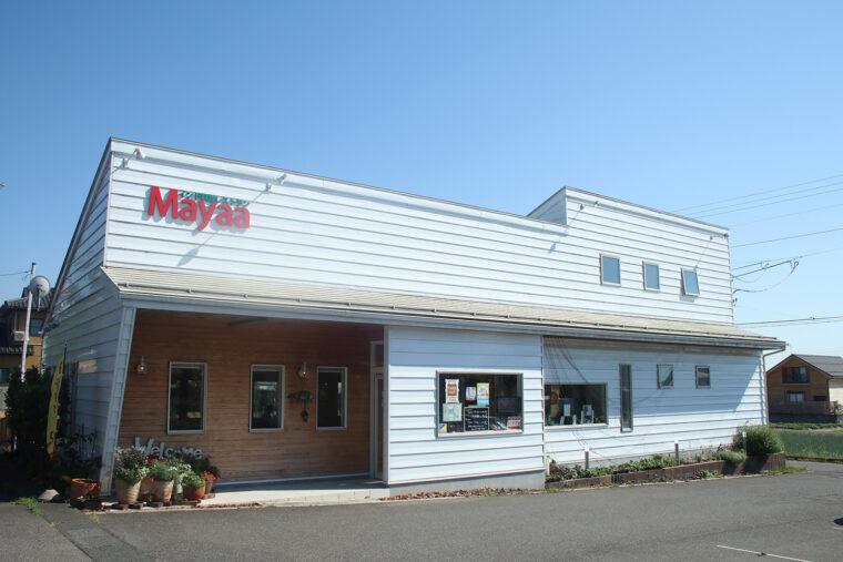 白い外壁に、赤い文字で「Mayaa」という文字が目印