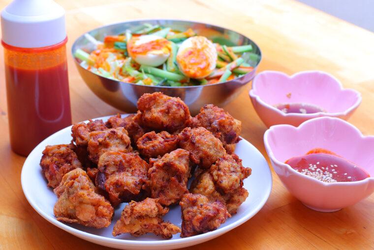 『韓国風チキン』(手前・1,500 円)と『チョルミョン』(奥・900 円)。皿に入ったタレはチキンのつけダレ、容器に入った赤いタレはチョルミョン用です